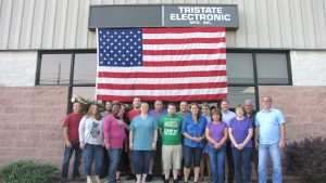 Tristate employees standing in front of a building with an American flag overhead.